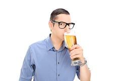 Junger Kerl, der ein halbes Liter Bier trinkt Stockbild