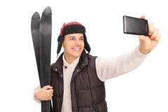 Junger Kerl, der ein selfie mit seinen Skis nimmt Stockbild