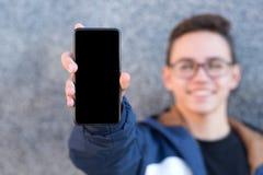 Junger Kerl, der ein Telefon auf grauem Hintergrund zeigt lizenzfreie stockfotos
