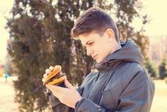 Junger Kerl, der einen Cheeseburger isst lizenzfreies stockfoto