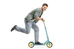 Junger Kerl, der einen Roller reitet und die Kamera betrachtet Lizenzfreies Stockfoto