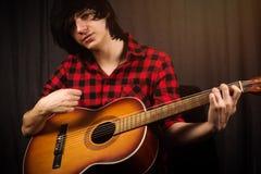 Junger Kerl, der Gitarre spielt Lizenzfreie Stockfotos