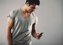 Junger Kerl, der hörende Musik auf Smartphone genießt Lizenzfreie Stockbilder