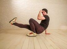 Junger Kerl in der Hip-Hop- und breakdance T?nzerhaltung der zuf?lligen Art im Studio auf Backsteinmauer lizenzfreies stockfoto
