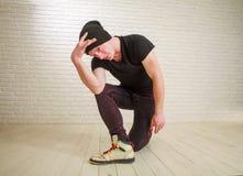 Junger Kerl in der Hip-Hop- und breakdance T?nzerhaltung der zuf?lligen Art im Studio auf Backsteinmauer lizenzfreie stockbilder