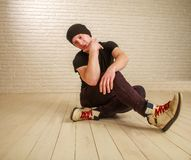 Junger Kerl in der Hip-Hop- und breakdance T?nzerhaltung der zuf?lligen Art im Studio auf Backsteinmauer stockbild