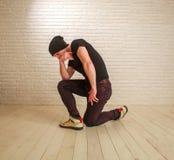 Junger Kerl in der Hip-Hop- und breakdance T?nzerhaltung der zuf?lligen Art im Studio auf Backsteinmauer stockfotos