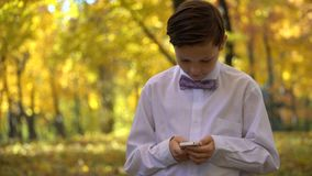 Junger Kerl, der im Telefon spielt und in den Herbstpark geht Stockbild