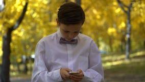 Junger Kerl, der im Telefon spielt und in den Herbstpark geht Stockfotografie