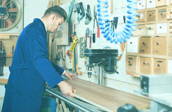 Junger Kerl, der Maschine verwendet, um Planke zu verarbeiten Stockbilder