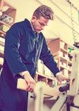 Junger Kerl, der Maschine verwendet, um Planke zu verarbeiten Stockbild