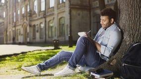 Junger Kerl der Mischrasse, der unter dem Baum, Kenntnisse im Notizbuch nehmend, Inspiration sitzt lizenzfreies stockbild