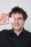 Junger Kerl, der mit seinem Führerschein lacht Stockbild