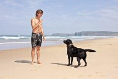 Junger Kerl, der mit seinem Hund spielt Stockbilder