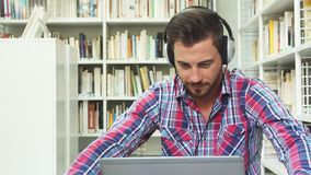 Junger Kerl, der Musik auf Kopfhörern auf Laptop hört stock video