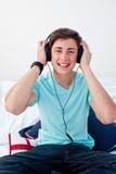 Junger Kerl, der Musik in seinem Schlafzimmer hört lizenzfreies stockbild