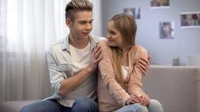 Junger Kerl, der schüchtern Freundin auf Sofa im Raum, in der Scheuheit und in der Unerfahrenheit umarmt lizenzfreies stockfoto