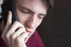 Junger Kerl, der am Telefon, unten schauend spricht lizenzfreies stockfoto