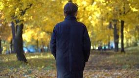 Junger Kerl in einem schwarzen Mantel im Herbstpark stock footage