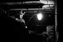 Junger Kerl in einer Arbeitsuniform und in Schutzhelmen, sitzend in einem niedrigen Tunnel lizenzfreie stockfotografie