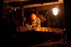 Junger Kerl in einer Arbeitsuniform und in Schutzhelmen, sitzend in einem niedrigen Tunnel stockbild