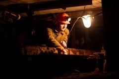 Junger Kerl in einer Arbeitsuniform und in Schutzhelmen, sitzend in einem niedrigen Tunnel lizenzfreie stockbilder