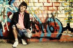 Junger Kerl gegen Graffitiwand. Lizenzfreie Stockfotos