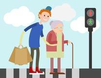 Junger Kerl hilft alter Frau, Straße zu kreuzen Stockfotografie