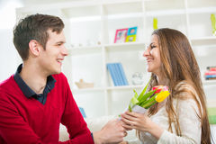 Junger Kerl holt seiner Freundin Blumen Lizenzfreie Stockfotos