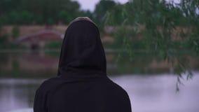 Junger Kerl im schwarzen Raglan und in einer gekleideten Haube stock video footage