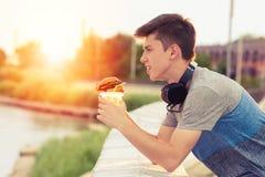 Junger Kerl ist, essend stillstehend und einen Burger bei Sonnenuntergang stockbilder