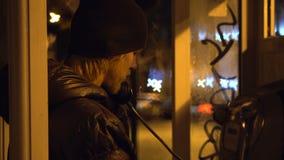 Junger Kerl ist, sprechend nennend und in der Telefonzelle an der Nachtstadt, kühles Wetter stock footage