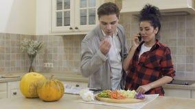 Junger Kerl kommt zu seiner Freundin, die das ` s, das am Telefon an der Küche spricht stock footage