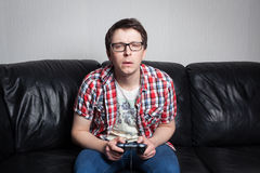 Junger Kerl mit den Gläsern und rotem Hemd, die Videospiele auf dem Steuerknüppel, sitzend auf einem schwarzen ledernen Sofa spie Stockbild