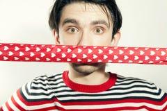 Junger Kerl mit einem Farbband am Mund Stockfotografie