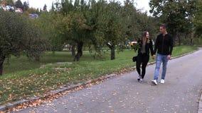 Junger Kerl mit einem Mädchenweg im Park, Händchenhalten stock video