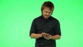 Junger Kerl mit Ihrem Telefon auf grünem Schirm stock footage