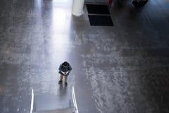 Junger Kerl mit intelligentem Telefon in seiner Hand in der Lobby des modernen buildi Lizenzfreie Stockbilder