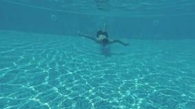 Junger Kerl schwimmt unter Wasser in einem Swimmingpool stock video