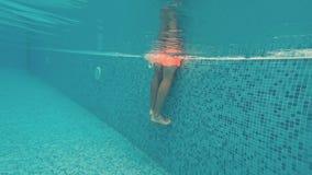 Junger Kerl schwimmt unter Wasser in einem Swimmingpool stock video footage