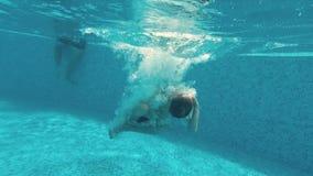 Junger Kerl schwimmt unter Wasser in einem Swimmingpool stock footage
