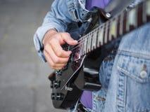 Junger Kerl singt Lieder und spielt Gitarre auf einer Jeansjacke in einem Park auf einem natürlichen Hintergrund Abbildung der el Stockbilder