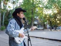 Junger Kerl singt Lieder und spielt Gitarre auf einer Jeansjacke in einem Park auf einem natürlichen Hintergrund Abbildung der el Lizenzfreie Stockfotografie