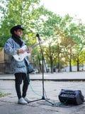 Junger Kerl singt Lieder und spielt Gitarre auf einer Jeansjacke in einem Park auf einem natürlichen Hintergrund Abbildung der el Lizenzfreie Stockfotos