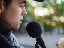 Junger Kerl singt Lieder und spielt Gitarre auf einer Jeansjacke in einem Park auf einem natürlichen Hintergrund Abbildung der el Stockfotografie