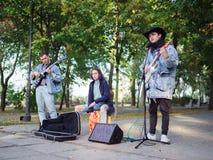 Junger Kerl singt Lieder und spielt Gitarre auf einer Jeansjacke in einem Park auf einem natürlichen Hintergrund Abbildung der el Stockfoto