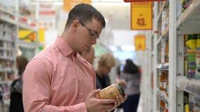 Junger Kerl wählt in Essig eingelegtes Gemüse in einem Speicher oder in einem Supermarkt Lizenzfreie Stockfotos