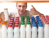 Junger Kerl wählt Milchprodukte im System aus Stockfotos