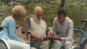 Junger Kerl zeigt alten Leuten, wie man die Tablette benutzt stock video footage