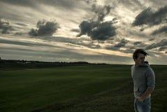 Junger Kerlaufenthalt auf dem Gebiet mit Wind Lizenzfreie Stockbilder